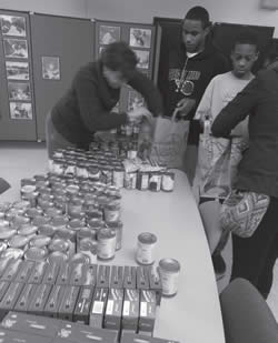SDC staff and youth assemble Thanksgiving food baskets of donated food for client families.