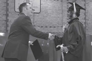 Reanne Brunson receives her GED/HSED certificate from Jake Gorges of SDC Education and Training Program.