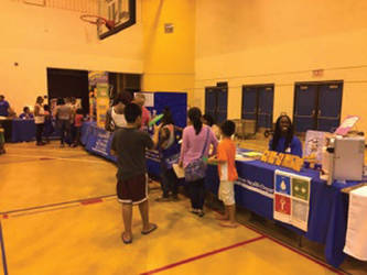Families stroll over health related booths during the 16th Annual Back-to-School Fair. (Photo by Dylan Deprey)